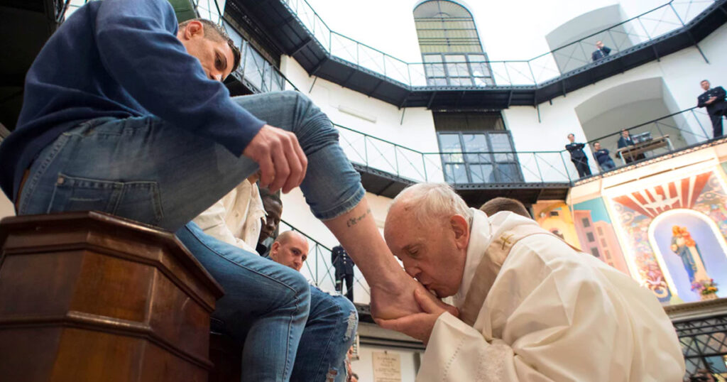 Paus Franciscus kust de voeten van een gevangene tijdens de viering op Witte Donderdag.