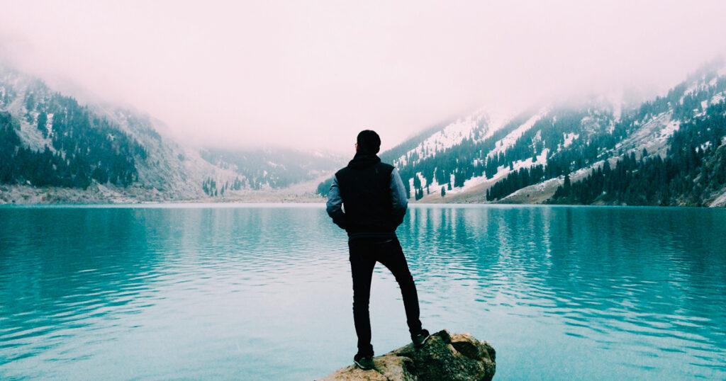 Man kijkend over een meer met op de achtergrond besneeuwde bergeen