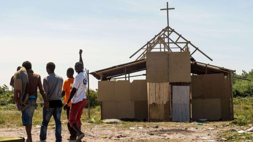 Wat is bidden? Foto van vluchtelingenkamp in Calais, waar schietgebedjes aan de orde van de dag zijn.